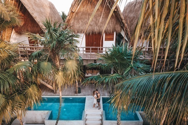 Onde ficar em Tulum: Bangalôs repletos de palmeiras, com piscinas embaixo e um casal se beijando