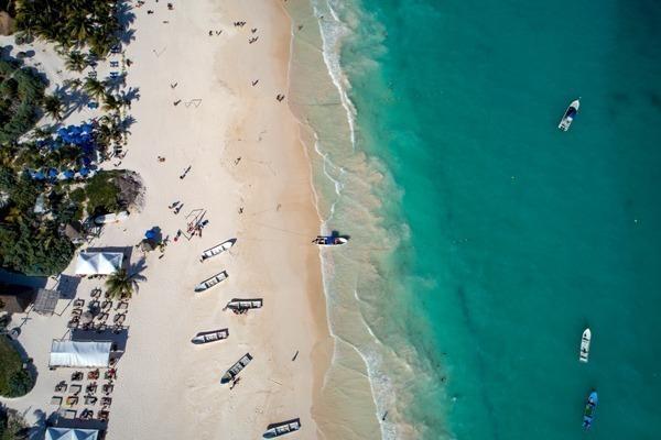 O último trecho da região hoteleira, com o Mar do Caribe azul a direita, a areia branca a esquerda, cheia de barquinhos e alguns restaurantes