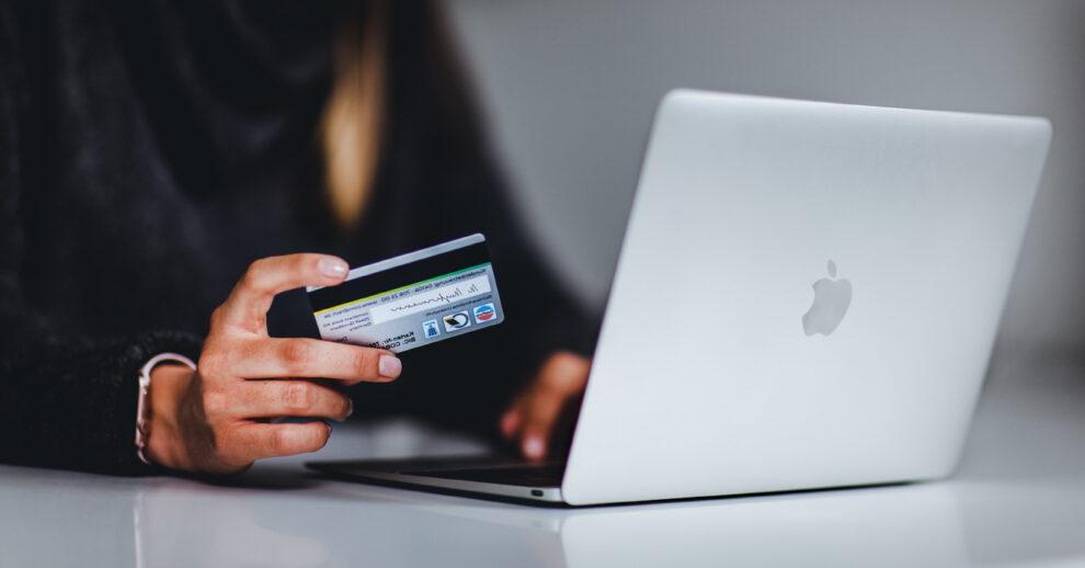 Como enviar dinheiro para Portugal: uma mulher segurando um cartão de crédito em frente ao computador