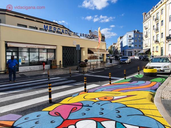O Mercado de Arroios, em Lisboa, um prédio bege com uma colorida arte de rua na frente da fachada, no chão