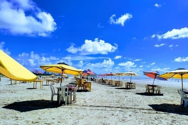 A Praia de Aruana cheia de mesas e guarda sóis e o ceú azul