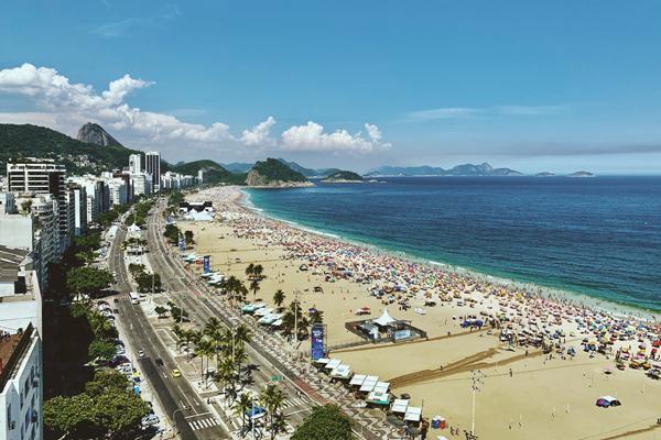 A Praia de Copacabana vista de algum apartamento, cheia de banhistas