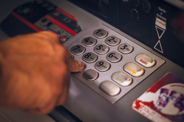 Uma mão mexendo num caixa eletrônico