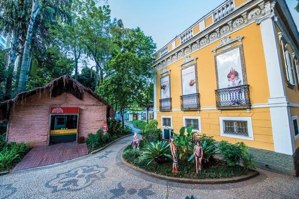 A fachada do Museu do Índio, com seu prédio amarelo e um no estilo de uma oca indígena