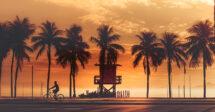 O que fazer em Copacabana: um homem andando de bicicleta no calçadão da praia, perto de um posto e cheio de coqueiros durante o pôr do sol