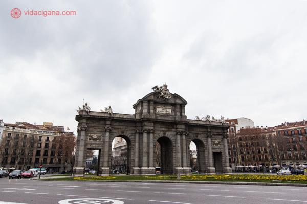 A Puerta de Alcalá vista da calçada, cercada de jardins verdes e floridos