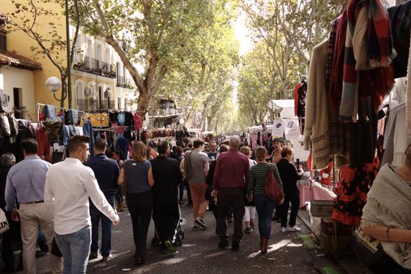 A rua onde fica o Mercado El Rastro, cheio de gente e bancas com os mais variados itens.