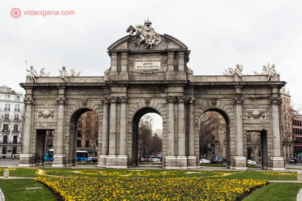 Onde ficar em Madrid: o Arco do Triunfo de Madri com flores amarelas no jardim ao redor