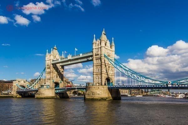 A Tower Bridge vista da margem do Rio Tâmisa num lindo dia de céu azul, amarelada e com os cabos azuis
