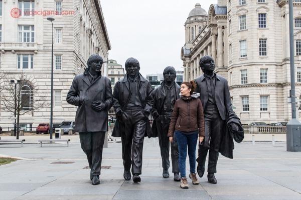 Uma mulher na frente da estátua dos quatro Beatles em Liverpool