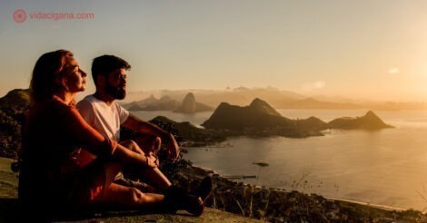 Onde ficar em Niterói: um casal sentado no Parque da Cidade, em Niterói, admirando o pôr do sol